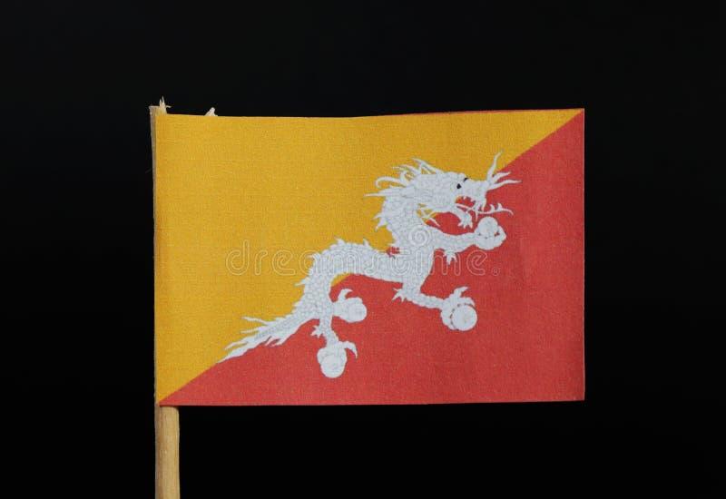 Официальный флаг Бутана на зубочистке на черной предпосылке Состоит из желтой и красной стороны с белым драконом стоковая фотография