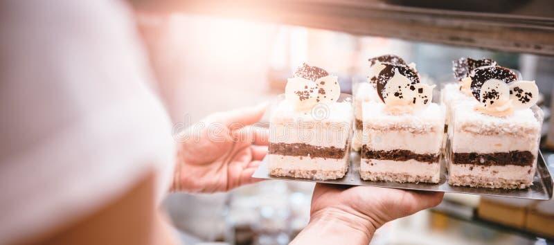 Официантка аранжируя торты стоковая фотография