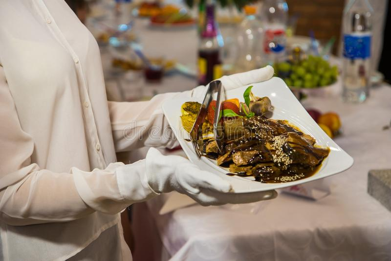 Официантка в белых перчатках держа плиту с диетой мяса намоченного коричневого соуса стоковое изображение rf