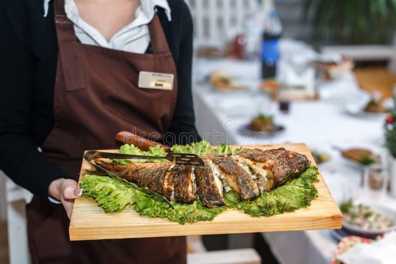 Официантка в черной форме держа деревянную плиту с испеченным fi стоковые фото