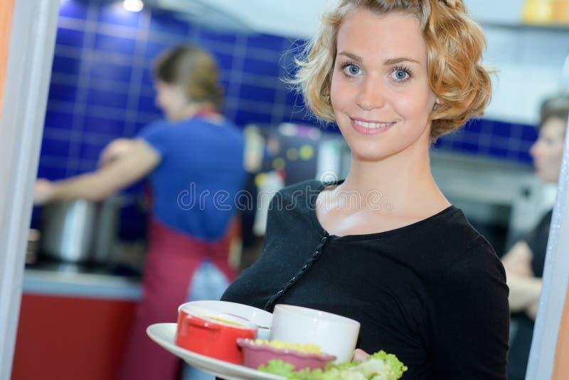 Официантка держа блюдо в ресторане стоковые изображения rf