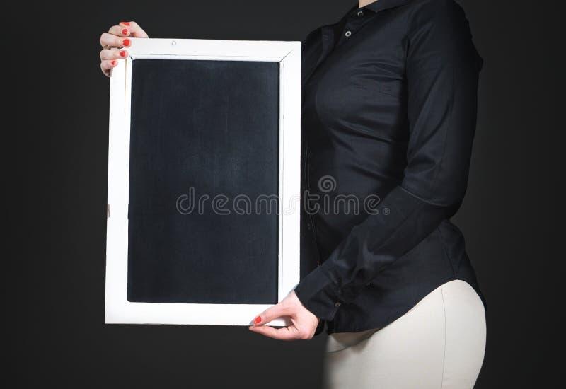 Официантка держа пустую доску Молодая профессиональная женщина в черной рубашке стоковая фотография rf