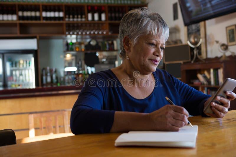Официантка используя ее мобильный телефон стоковое фото rf