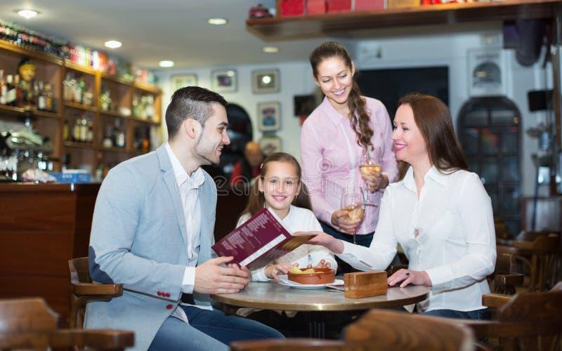 Официантка и семья на кафе стоковое изображение