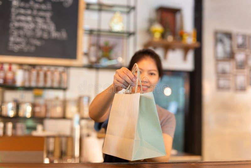 Официантка на счетчике давая eco дружелюбный бумажный мешок с взятием прочь выпивает в кафе стоковая фотография rf