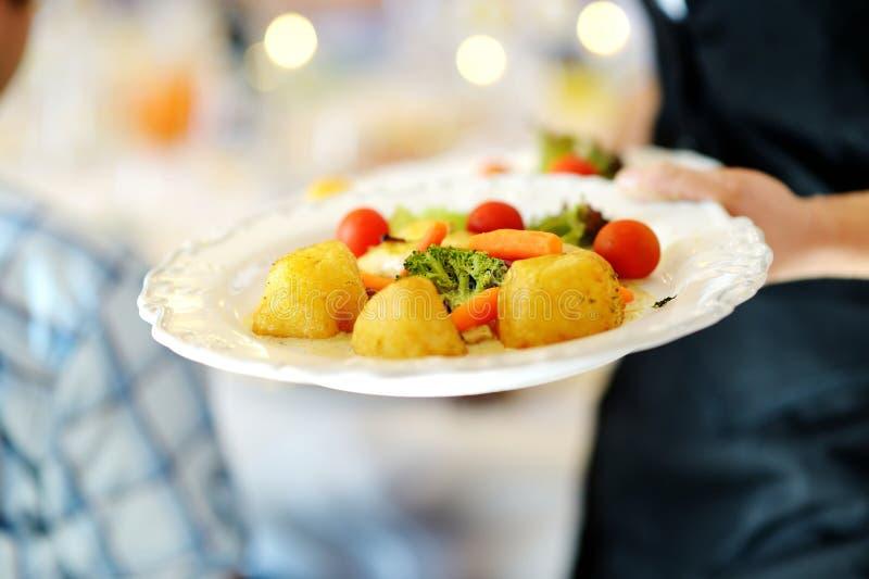 Официантка нося плиту с блюдом veggie стоковое фото