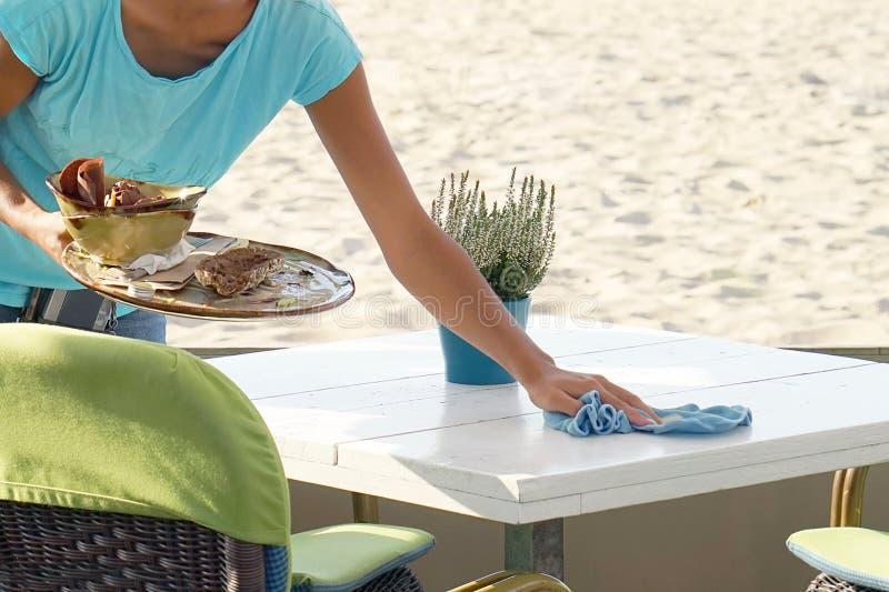 Официантка обтирая таблицу в кафе стоковое фото