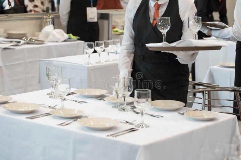 Официантка одетая в форме служа набор стекел стоковое фото