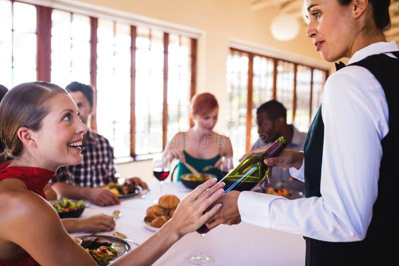 Официантка показывая вино к клиенту на таблице стоковое фото