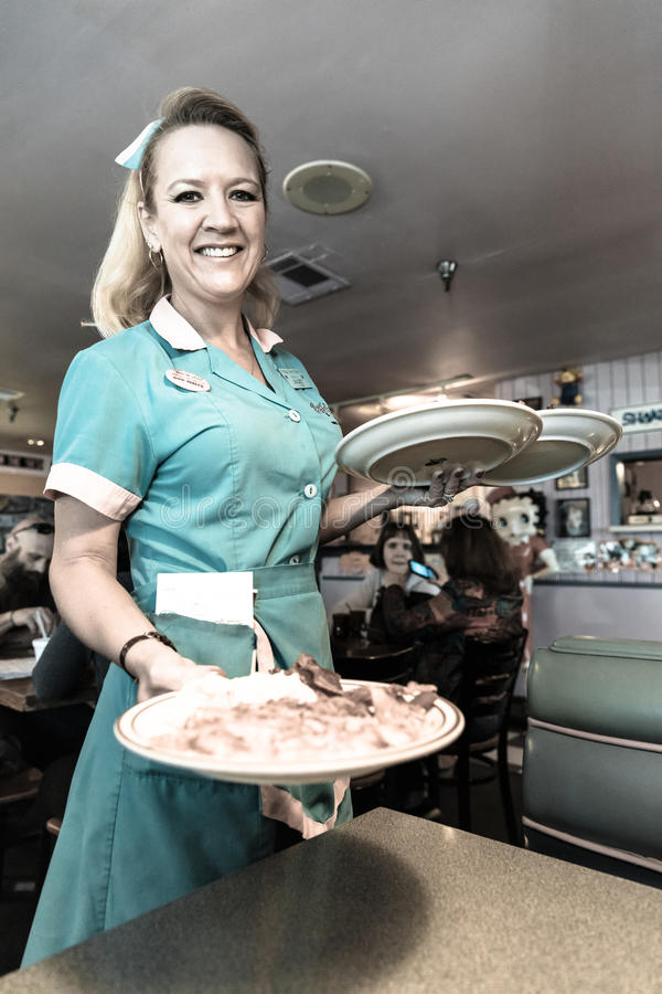 Официантка поставляет завтрак на обедающем трассы 66 Пегги Сью Американа воодушевленном в Yermo, Калифорнии о 8 милях вне бара стоковая фотография