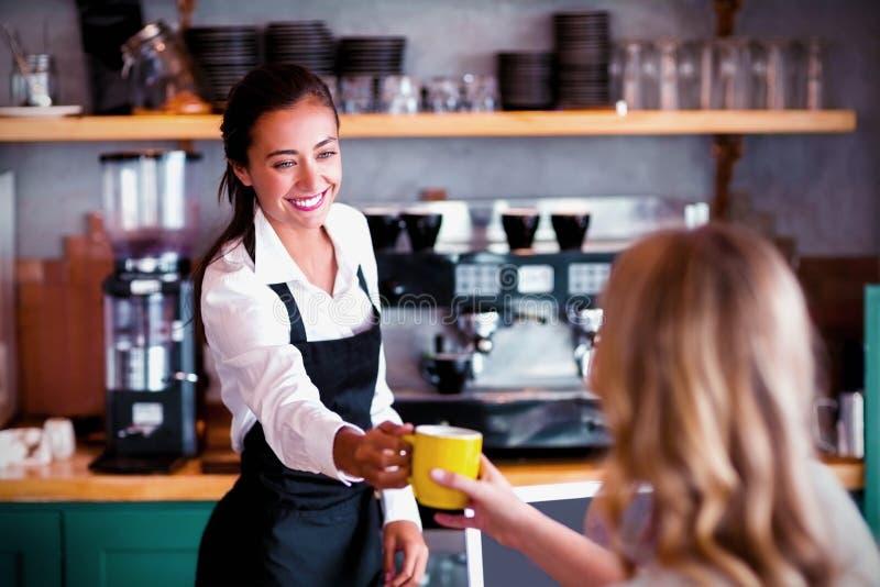 Официантка предлагая чашку кофе стоковые фото