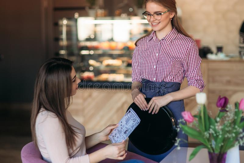 Официантка принимая заказ от ее клиента в кафе стоковое изображение rf