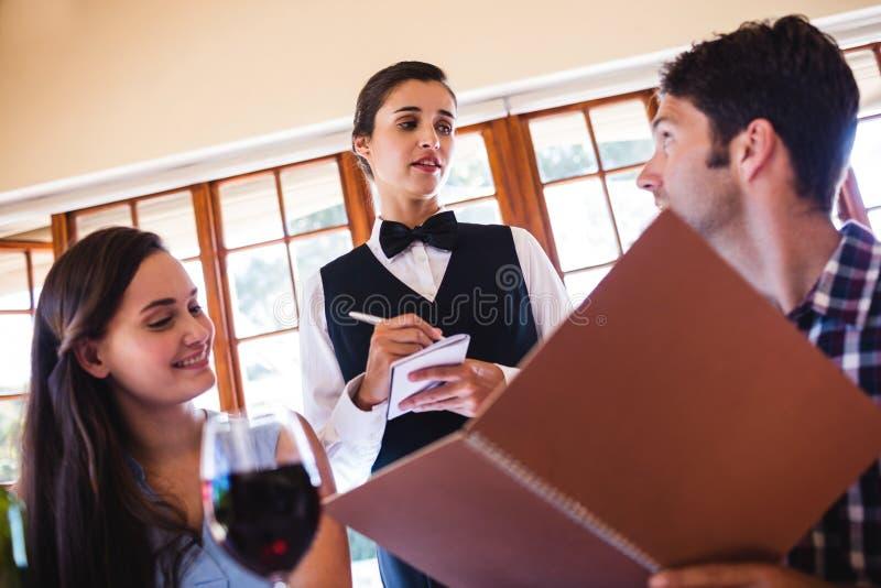 Официантка принимая заказ от пары стоковое изображение