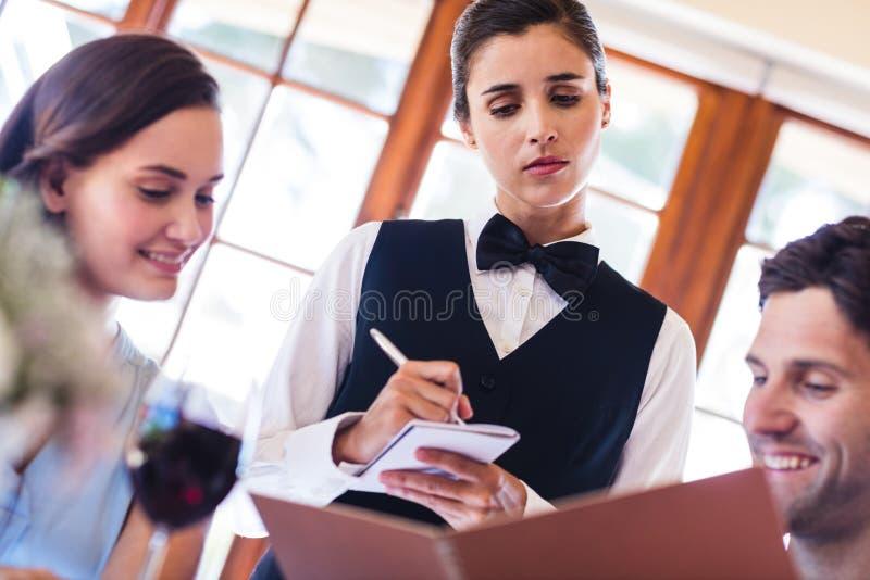 Официантка принимая заказ от пары стоковые фото