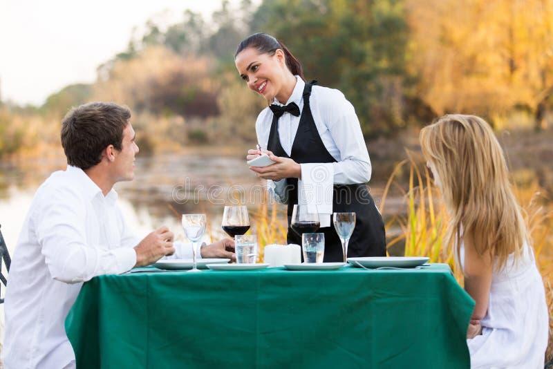 Официантка принимая клиента заказа стоковое фото