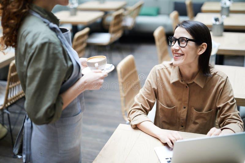 Официантка принося кофе к коммерсантке стоковые фотографии rf