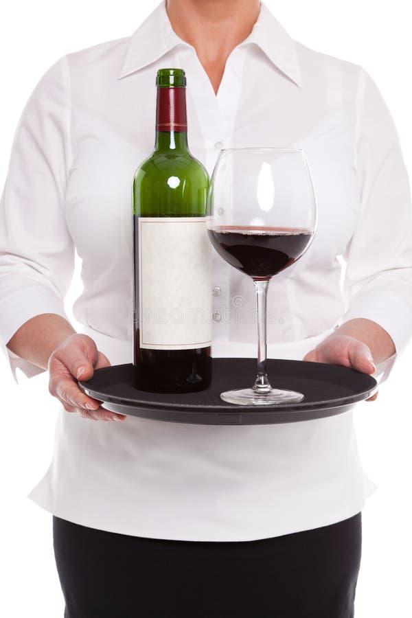 Официантка служя красное вино с стеклом и бутылкой на подносе. стоковая фотография