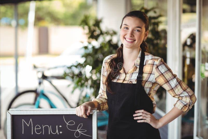 Официантка стоя с доской меню вне кафа стоковое изображение