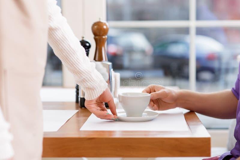 Официантка служа кофе pf чашки стоковые фото
