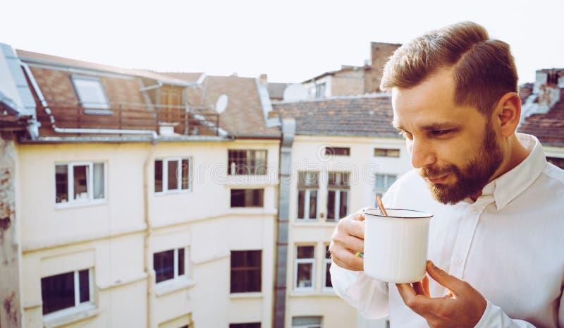 Официант в балконе принимая кружку кофе Красивый турецкий парень с бурым медведем стоковая фотография