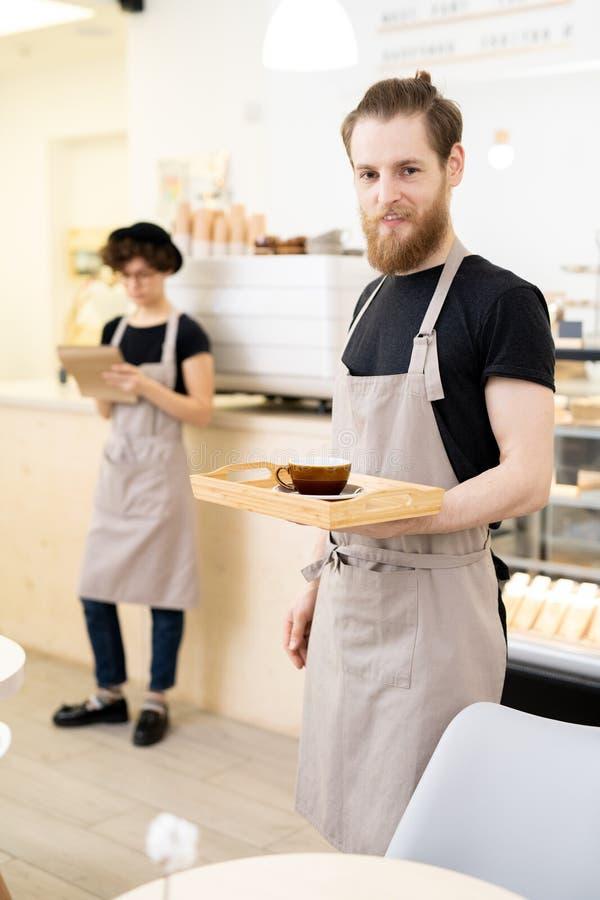 Официант подноса нося кофейни с чашкой стоковые изображения