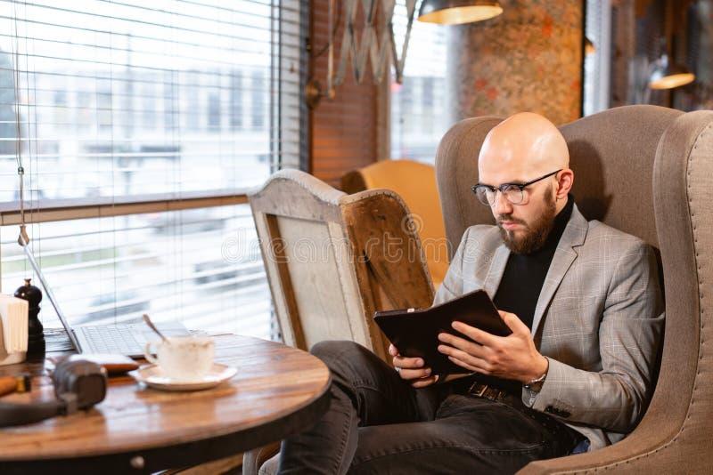Официант приносит электронные меню или счет в ресторане в форме планшета смартфона, с встроенным стоковое изображение rf