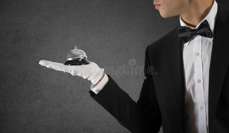 Официант с колоколом в руке Концепция обслуживания первого класса в вашем деле стоковая фотография