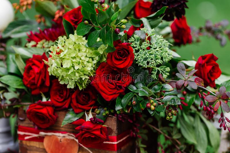 Оформление таблицы свадьбы: цветет состав при розы, ягоды, травы и растительность стоя в деревянной коробке Bridal детали и decor стоковое фото rf