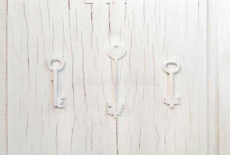 Оформление на старой серой треснутой двери, винтажный абстрактный дизайн 3 ключей ультрамодное стоковое фото