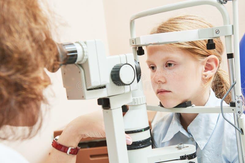 Офтальмология ребенка женский доктор проверяет зрение на девушке стоковое фото rf