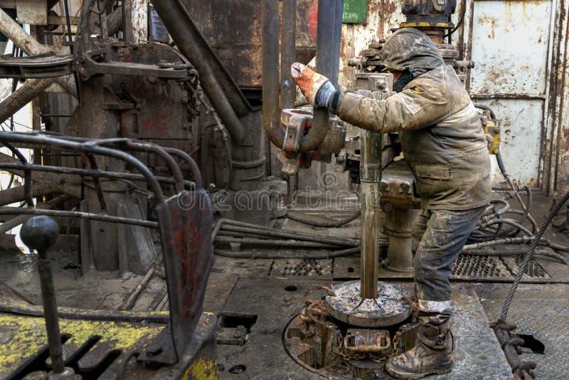 Оффшорный работник буровой вышки подготавливает инструмент и оборудование для нефтяной скважины нефти и газ прокалывания на платф стоковая фотография rf