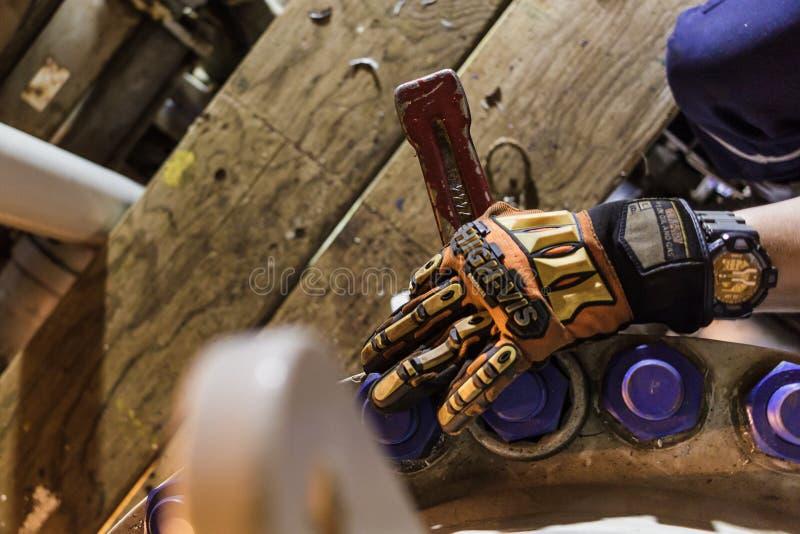 Оффшорный работник держа ключ молотка стоковые изображения rf