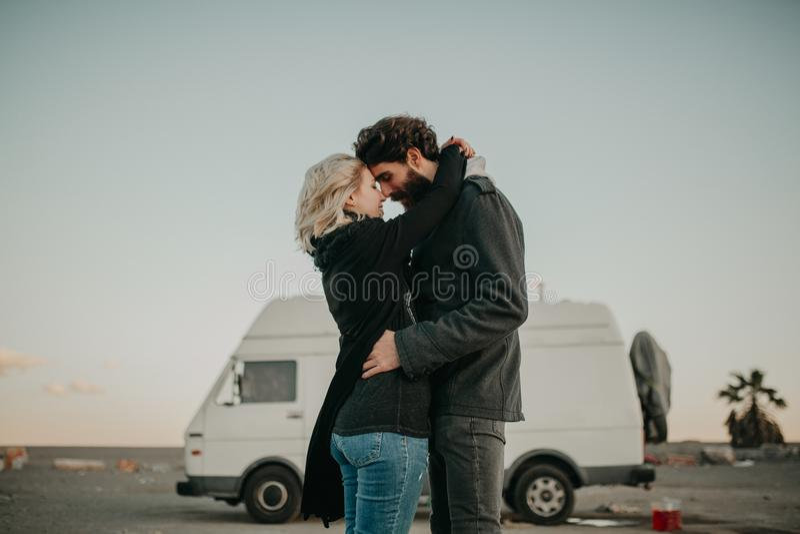 Охладите один другого молодых пар целуя outdoors пока они обняты, во время стопа поездки, с их фургоном на заднем плане стоковое фото rf