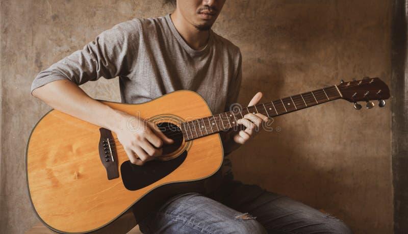 Охлаждающ и играющ акустическую гитару в комнате стоковое фото