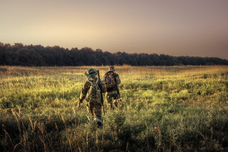 Охотники с охотиться оборудование идя прочь через сельское поле к лесу на заходе солнца во время сезона звероловства в сельской м стоковые фото