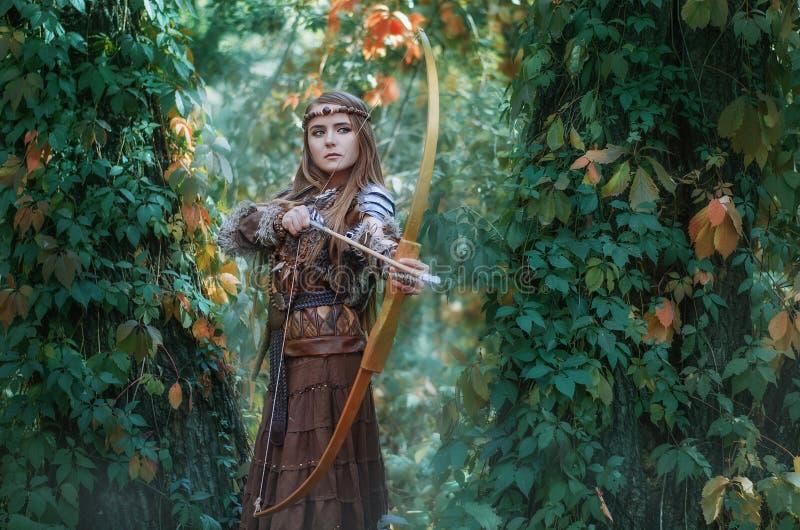 Охотник женщины с смычком в руке, принимая цель на его добычу в лесе Амазонке стоковые изображения rf