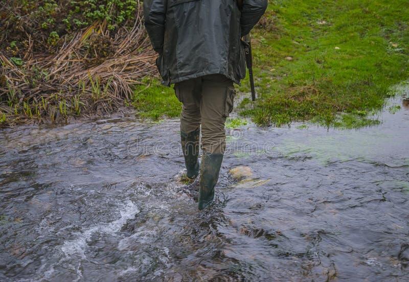 Охотник со сквозным винтовки passe река стоковые изображения