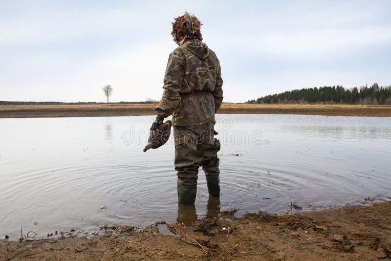 Охотник с decoy утки в его стойках руки на береге стоковые изображения rf