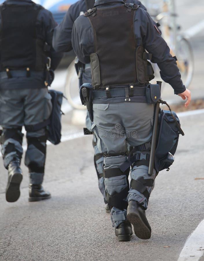 охраните патруль в полиции по охране общественного порядка с оружием и пистолетом во время протеста стоковое фото