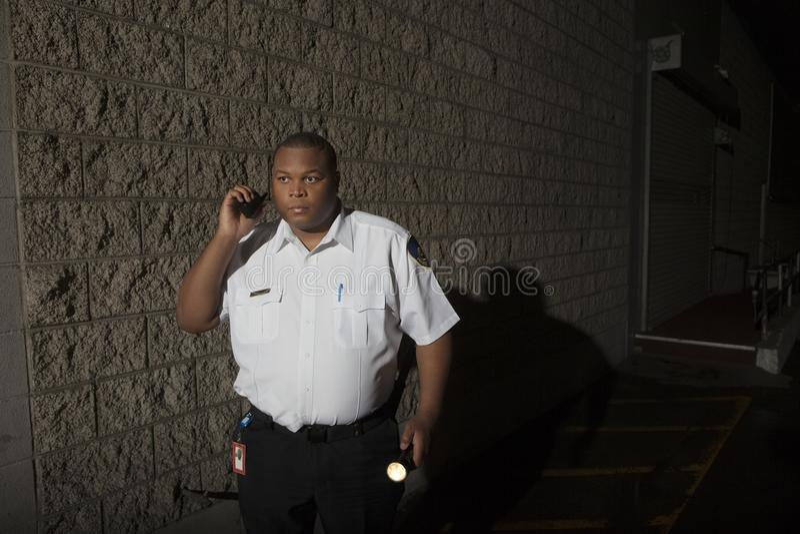 Охранник с звуковым кино и факелом Walkie патрулирует на ноче стоковые фотографии rf