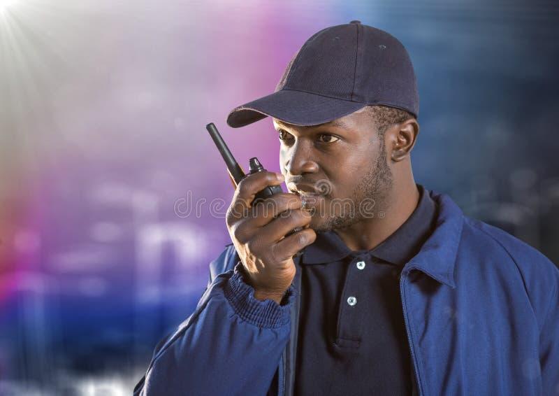 Охранник с звуковым кино walkie против расплывчатой стены с эскизом и пирофакелом здания стоковое изображение rf