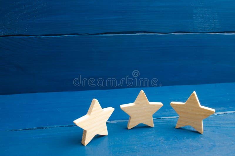 Оценка гостиницы, ресторана, передвижного применения 3 звезды на голубой предпосылке Концепция оценки и оценки стоковая фотография rf