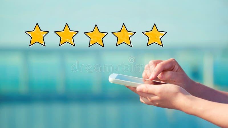 Оценка 5 звезд при персона держа smartphone стоковые фото