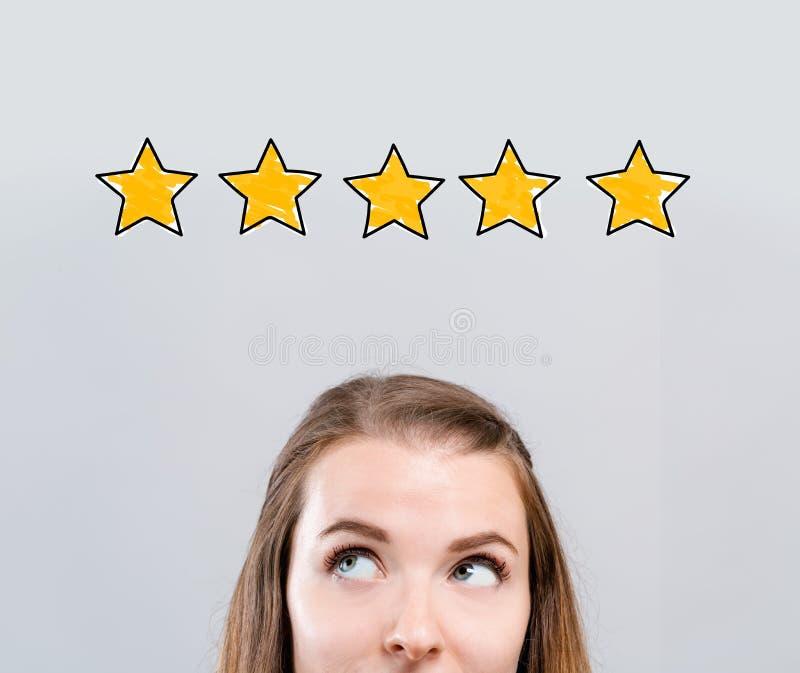 Оценка 5 звезд с молодой женщиной стоковое изображение rf