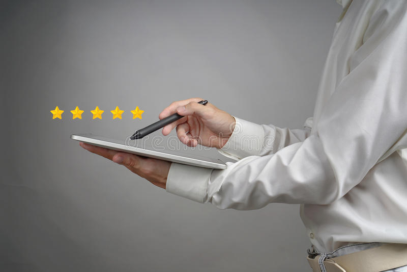 Оценка или ранжировка 5 звезд, проверять концепция Человек с ПК таблетки определяет обслуживание, гостиницу, ресторан стоковая фотография