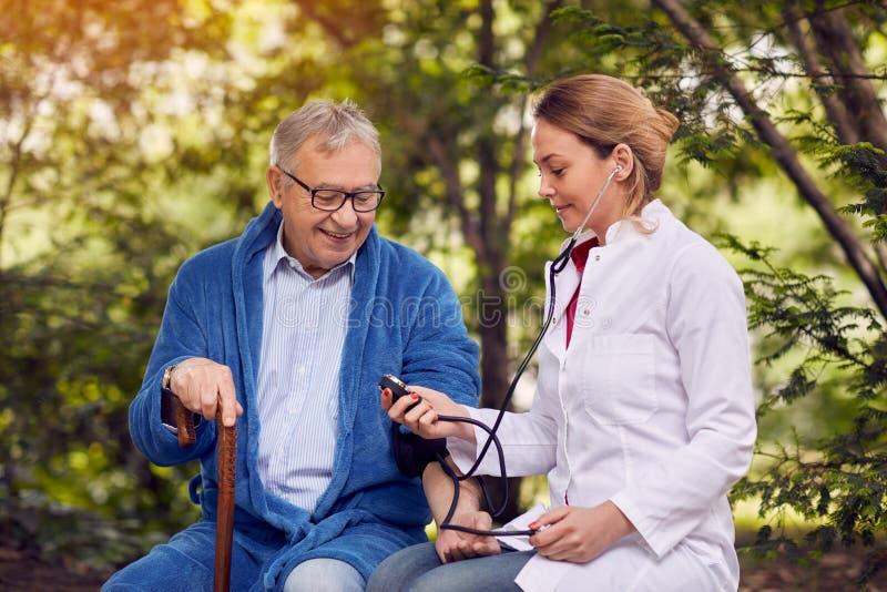 Оценка медсестры человека кровяного давления пожилого усмехаясь стоковое изображение