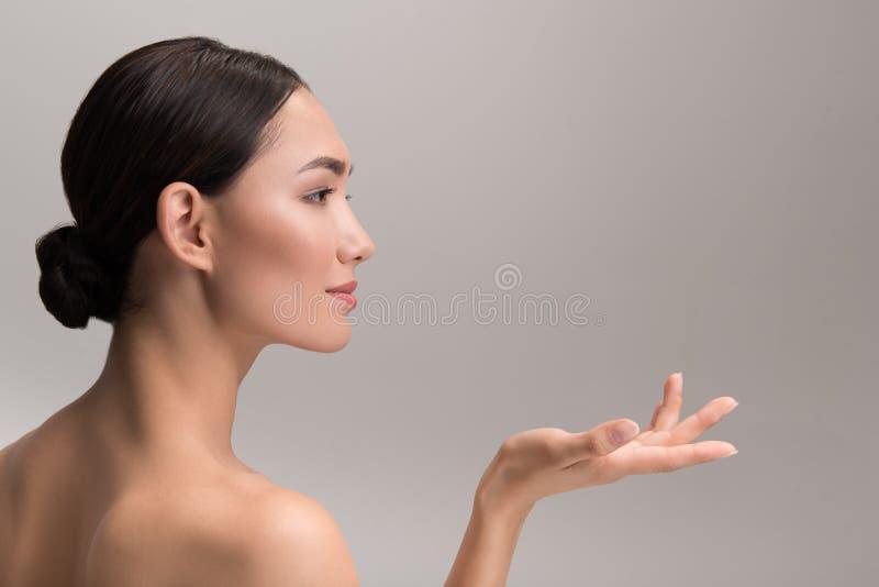 Очаровательная дама держит незримый продукт в руке стоковая фотография rf