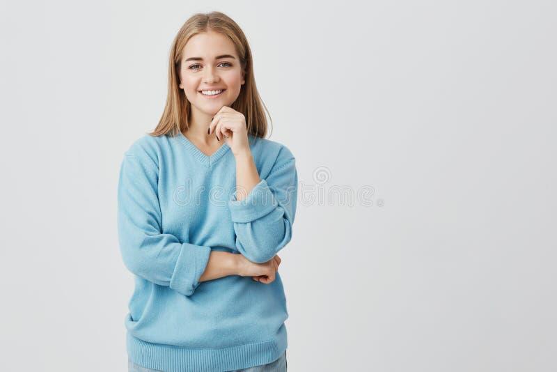 Очаровательная девушка одела в голубой усмехаться с белыми зубами, держащ руку под подбородком, думая о планах на каникулы стоковая фотография rf