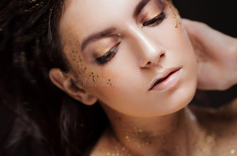 Очаровательная девушка с модным блестящим макияжом, модный макияж с зо стоковая фотография