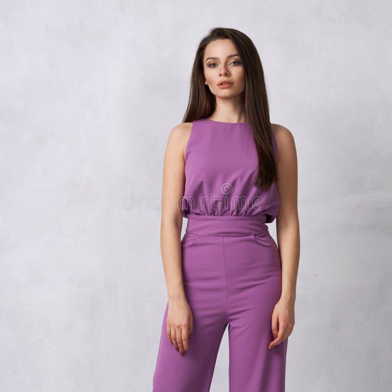 Очаровательная женская модель в фиолетовом комбинезоне стоковые изображения